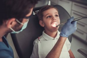 boy open mouth for doctor doing oral examination at medical clinic stock photo