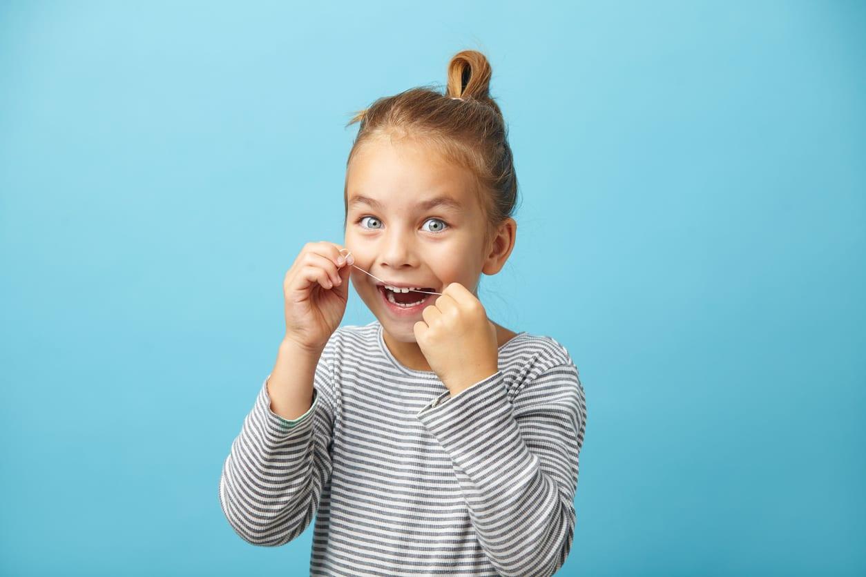 Little girl flossing her teeth